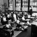 Students seated at desks, raising their hands as a young girl recites and a nun observes in a...