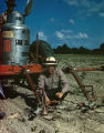 Price C. McLemore and another man inspecting a Sizz-Weeder on McLemore's Oaks Plantation in...