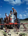 Price C. McLemore and another man examining the fuel tank of a Sizz-Weeder on McLemore's Oaks...