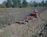 African American man on a red McCormick-Deering Farmall Cub tractor, plowing a field on Price...