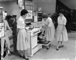"Three women baking cakes for a demonstration during the Alabama Gas Corporation's ""Old Stove..."