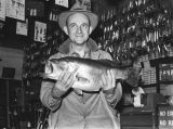 Norman Span holding up a bass in a fishing store.