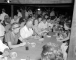 Guests eating at long tables under a pavilion during the Montgomery Lumbermen's Club barbecue.