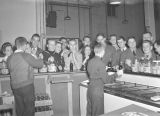 Servicemen at a USO dance, standing at a counter for refreshments.
