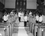 Members of the Von Seeburg-Sanford wedding party, standing in front of the altar in the main...