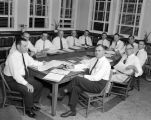 Men sitting around a table during a meeting at Alabama Christian College in Montgomery, Alabama.