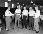 Man making a presentation to four employees during a meeting at the Alabama Power Company...