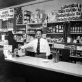 Isaac Hasson standing behind the counter of his store, Hasson's Delicatessen, at 308 North Arthur...