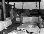 African American man asleep on cardboard boxes at a railroad station.