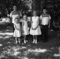 Two grandsons and three granddaughters of Aubrey Williams in front of a tree.
