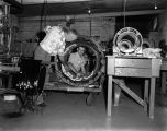 Two men examining a motor at the Standard Electric Machine Works on North Decatur Street in...
