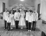 Members of the Nielsen-Know wedding party, standing in front of the altar in a church building.