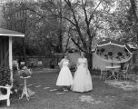 Miss Cottle and another young lady in formal gowns, standing in a backyard before a graduation...