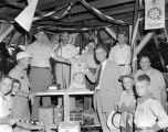 Men and boys gathered around a bag of crimson clover seed at an auction at the Lions barbecue at...