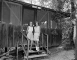 "Two girls standing on the steps of ""Anne's House,"" a cabin at the Y.W.C.A.'s Camp..."