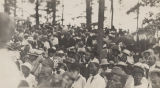 Audience of African American men and women in the woods in rural Alabama, probably listening to an...