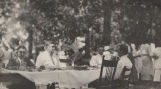 J. L. Sibley and three other men, eating at a table in the woods in rural Alabama.