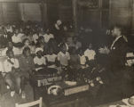 African American man giving a health lecture to an audience of adults and children, probably in a...