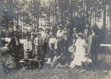 Group of adults and children in the woods.