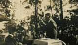 Booker T. Washington addressing an audience of educators and school agents outdoors in Coosa...
