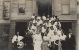African American men and women, probably teachers, standing on the steps of a wooden school...