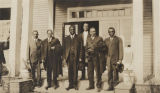 Group of men standing in front of an African American school building in rural Conecuh County,...