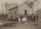 Children and adults standing outside the school building in District 43 of Escambia County,...