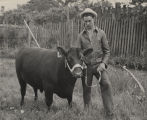 E. J. Klinner and his bull, which was the grand champion at a beef cattle show and sale in...