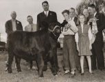 Governor Jim Folsom with a young boy and his prize-winning bull at a livestock show and sale in...