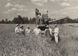 Men standing around a John Deere combine in a field of grains in Alabama.