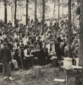 Men and women seated on benches in a wooded area, during the annual field meeting at the Black...