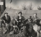 Five men with three hunting dogs, seated in front of a tent in a wooded area.