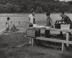 Man speaking to two women at a picnic table beside a lake in Alabama.