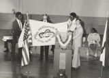 Men holding up the flag of the American Revolution Bicentennial in a school gymnasium.