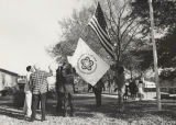 Men raising the flag of the American Revolution Bicentennial outside a school.