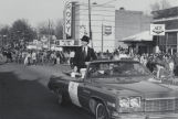 Paul Harvey riding in a convertible, as the grand marshal of a Christmas parade in downtown...