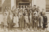 Group of African American women standing in front of a brick building, possibly a school.