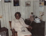 Ruth Datcher seated in a wooden chair indoors.