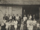 Members of the Mullenix family gathered in front of a dogtrot house.
