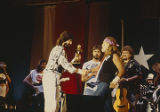 Randy Owen, of the group Alabama, shaking hands with Willie Nelson while on stage.