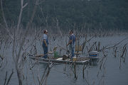 Man and two boys fishing from a boat at Bear Creek Lakes in Franklin County, Alabama.