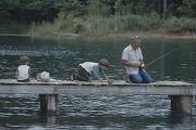 Man and two boys fishing from a pier at Bear Creek Lakes in Franklin County, Alabama.