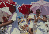 Little girls carrying umbrellas or parasols in the Street Struttin' parade through downtown...