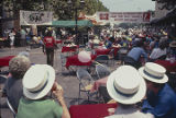 People seated at tables in a street in downtown Florence, Alabama, during the W. C. Handy Music...