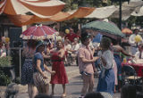People dancing and holding umbrellas or parasols during the Street Struttin' parade at the W. C....