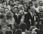 George Wallace speaking at a microphone in the middle of a crowd.