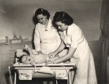 """Auburn girls learn practical problems of infant care at the nursery school."""