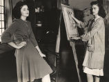 """Nancy Greer (right) has persuaded Ann Johnson to pose for a class in clothes designing...."