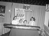 "Children standing with ""The World's Largest Beef Hot Dog!"" at Garrett Coliseum during..."