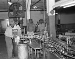 Employees packing cans of Alaga Syrup into boxes at the Alabama-Georgia Syrup Company, in...